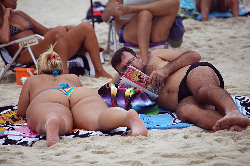 Девушка на пляже берет в рот